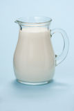Jug with fresh milk on a blue Stock Images