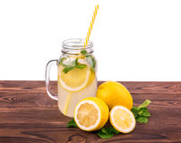 The jug full of mojito with ripe and juicy lemon, fresh mint on a brown wooden table, isolated on a white background. Royalty Free Stock Photography