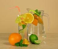 Jug, glass with cocktail, orange and a juicy lime Royalty Free Stock Photos