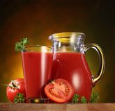 Jug and glass full of tomato juice. royalty free stock images