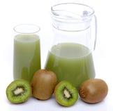 Jug and glass of kiwi juice and some fresh kiwis. Isolated on white Stock Image