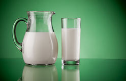 Jug and glass with milk. On green background Stock Photos