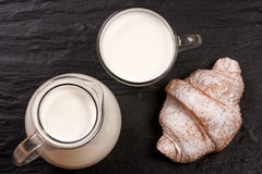 Jug and a glass of milk with a croissant on a black stone background. Top view Royalty Free Stock Image