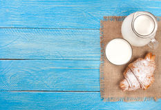 Jug and glass of milk with croissants on a blue wooden background with copy space for your text. Top view Royalty Free Stock Photo