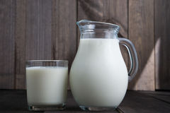 Jug and glass with milk. Full jug and glass with milk on wooden background Stock Photo