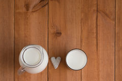 Jug and glass with milk. Full jug and glass with milk on wooden background and cookie heart Royalty Free Stock Images