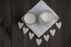 Jug and glass with milk , heart cookies. Jug and glass with milk and heart cookies on white tissue napkin and wooden background Stock Photography