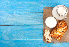 Jug and glass of milk with a loaf of bread on a blue wooden background with copy space for your text. Top view Stock Photography