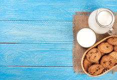 Jug and glass of milk with oatmeal cookies on a blue wooden background with copy space for your text. Top view Stock Photography