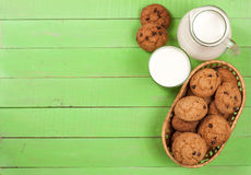 Jug and glass of milk with oatmeal cookies on a green wooden background with copy space for your text. Top view Stock Images