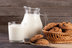 Jug and glass of milk with oatmeal cookies in a wicker basket on a wooden background.  royalty free stock photo