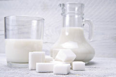 Jug and glass with milk and sugars Royalty Free Stock Photos