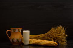 Jug, glass of milk, white bread and a sheaf on a black background, with space for text Stock Image