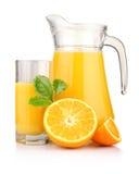 Jug, glass of orange juice and orange fruits i Royalty Free Stock Images