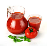 Jug, glass of tomato juice and fruits with green leaves Royalty Free Stock Images