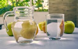 Jug and glass of water with fruits from behind royalty free stock photography