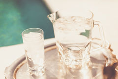 Jug and glasse of water by the pool Royalty Free Stock Image