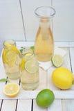Jug and glasses with lemonade, lemons and lime on rustic table Stock Photography