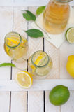 Jug and glasses with lemonade, lemons and lime on rustic table Stock Photo