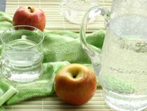 jug and glasses with water and apple Stock Photos