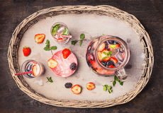 Jug and glasses with water ,berries and Ice cubes on rustic wooden background, top view. Royalty Free Stock Image