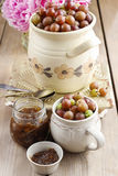 Jug of gooseberries on wooden table Stock Photos