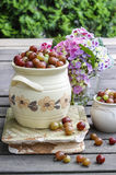 Jug of gooseberry on wooden table Stock Photos