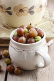 Jug of gooseberry on wooden table Stock Images