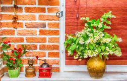 Jug with jasmine flowers. On a background of blinds and brick wall. interior, kitchen. Photo in old image style Stock Images