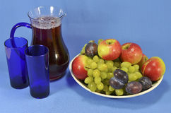 Jug with juice and fruit on a platter. Pitcher with fruit juice, two glasses and fruits on a platter on a blue background Stock Photos