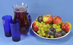 Jug with juice and fruit on a platter. Pitcher with fruit juice, two glasses and fruits on a platter on a blue background Stock Photo