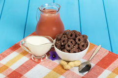 Jug of juice, yogurt, corn rings with cocoa and sesame seeds, peanuts, spoon on blue. Stock Photo