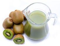 Jug of kiwi juice and some fresh kiwis. Isolated on white Royalty Free Stock Photo