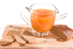 Jug with kvass (kvas), bread and ears on wooden board. Jug with homemade traditional russian grain drink - kvass (kvas), black rye bread and ears on wooden Stock Photos