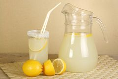 Jug of lemonade. Jug and glass of lemonade on a wooden table Stock Photos