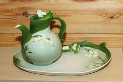 Jug with lilies of the valley on a platter. Royalty Free Stock Photos