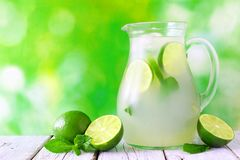 Jug of limeade against a green outdoor background Stock Photo