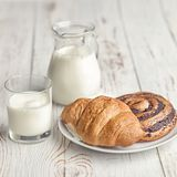 A jug of milk and an appetizing croissant on a village table in the morning ligh stock photography