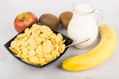 Jug of milk, bowl with corn flakes and fruits Stock Photos