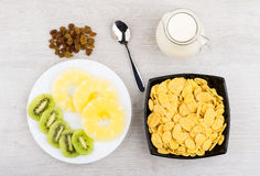 Jug of milk, bowl with corn flakes, pineapple and kiwi Royalty Free Stock Photography