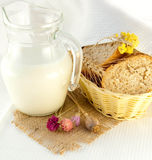 Jug with milk, bread and wild flowers Royalty Free Stock Photos