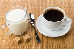 Jug of milk, sugar, cup with coffee and spoon Stock Image