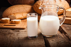 Jug with milk. Closeup on background bread Royalty Free Stock Image