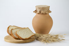 Jug of milk with freshly baked white bread and wheat ears. Stand Royalty Free Stock Photo
