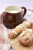 A jug with milk and lye pastry on the wooden board. Selective focus Stock Photography