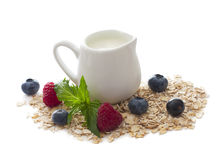 Jug of milk and oats. With fresh berries isolated over white Royalty Free Stock Image
