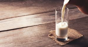 Jug of milk with an old country table, a white drink is poured i. Nto a glass royalty free stock photo