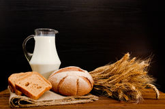 Jug of milk, round rye bread, a sheaf of wheat and bread slices on sackcloth. Wooden table Royalty Free Stock Photo