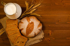Jug with milk, round and square rye bread and ears on the wooden table, top view Stock Photos