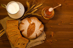 Jug with milk, rye bread, ears, honey, on wooden table, top view Stock Images